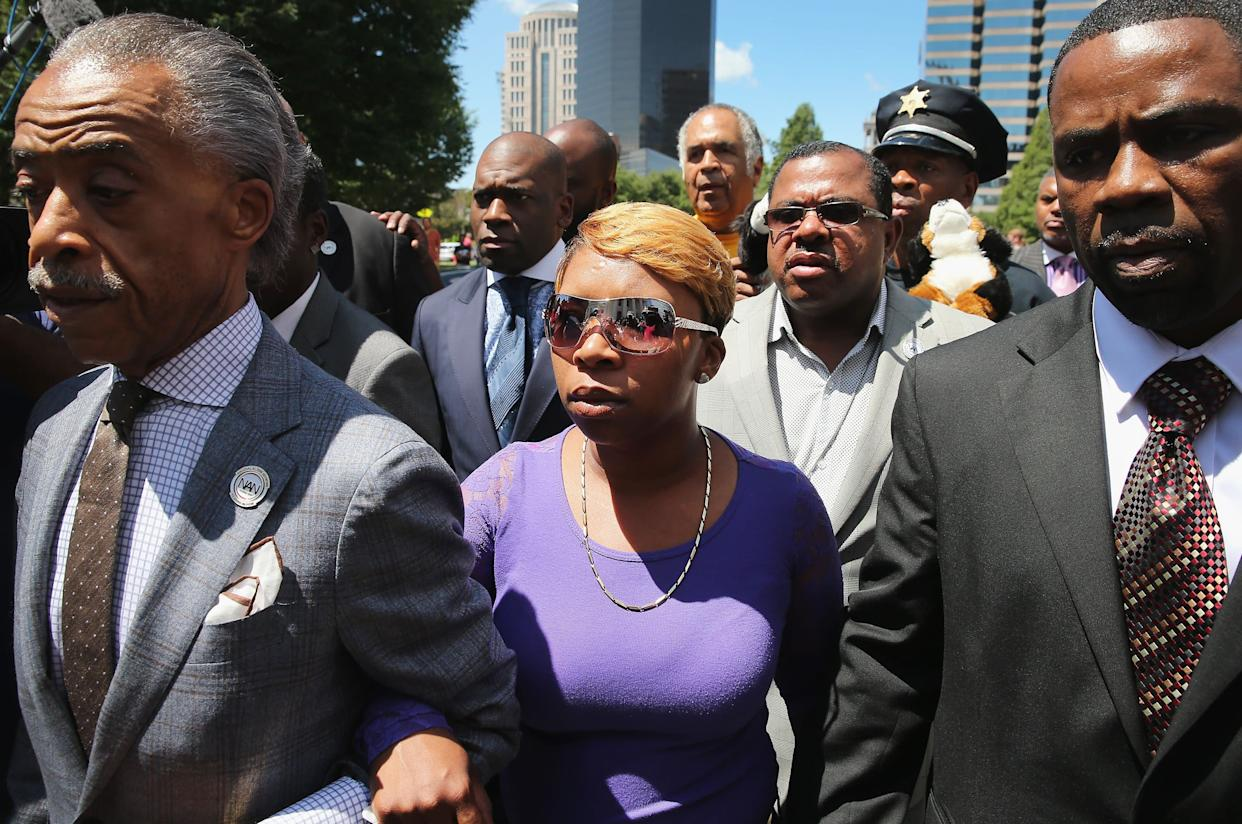 ST. LOUIS, MO - AUGUST 12: Lesley McSpadden (C), the mother of slain teenager Michael Brown, arrives for a press conference on the arm of civil rights leader Rev. Al Sharpton (L) on August 12, 2014 in St. Louis, Missouri. Brown was shot and killed by a police officer on Saturday in suburban Ferguson, Missouri. Sharpton and Browns family were calling for order following riots and skirmishes with police over the past two nights in Ferguson by demonstrators angry over the shooting. (Photo by Scott Olson/Getty Images)