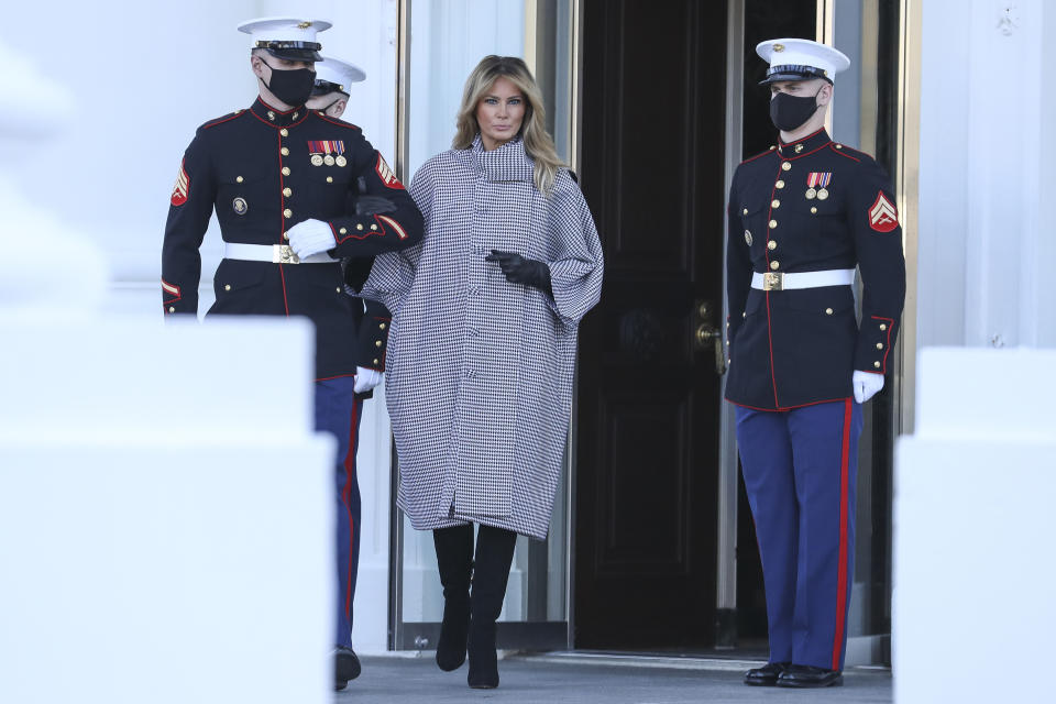 First Lady Melania Trump arrives to receive the White House Christmas tree at the White House on Monday, November 23, 2020 linking arms with a soldier