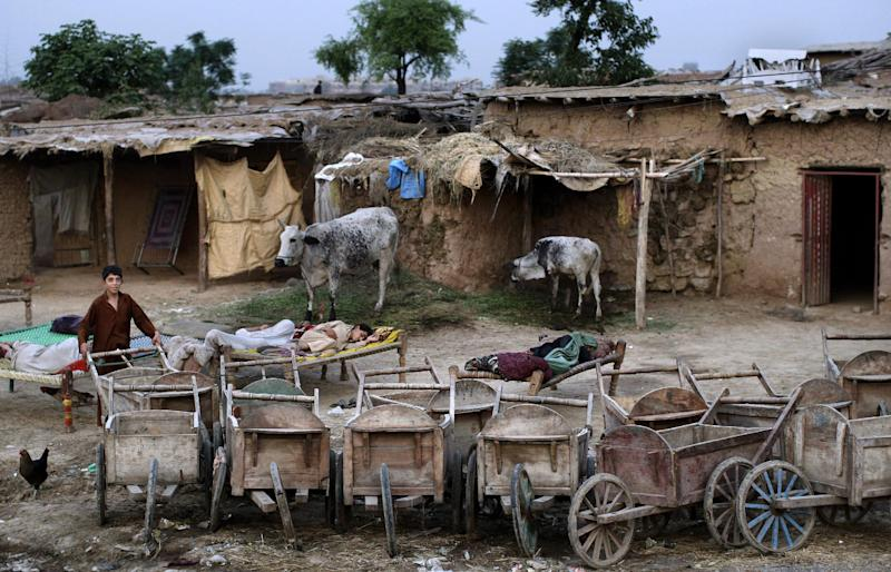 In this Wednesday, Aug. 8, 2012 photo, an Afghan refugee youth, left, pulls a wooden cart parked with other carts next to other refugees sleep on beds outside their homes, to escape the heat trapped in their homes during the summer months, in a slum area on the outskirts of Islamabad, Pakistan. Hundreds of thousands of Afghan refugees are in limbo as Pakistan, increasingly frustrated with hosting the world's largest and longest-running refugee population, weighs whether to renew their refugee status by the end of this year. A large-scale return of the 1.7 million Afghan refugees currently living in Pakistan would be a massive problem for Afghanistan at a time when it's already struggling to maintain security in the face of an American troop withdrawal. But Pakistan increasingly seems to be angry at a refugee population that many feel has overstayed its welcome. (AP Photo/Muhammed Muheisen)