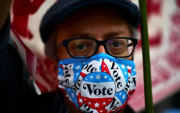 "A man wearing a protective face mask with the message ""Vote"" takes part in a rally outside of the Philadelphia Convention Center - REUTERS"