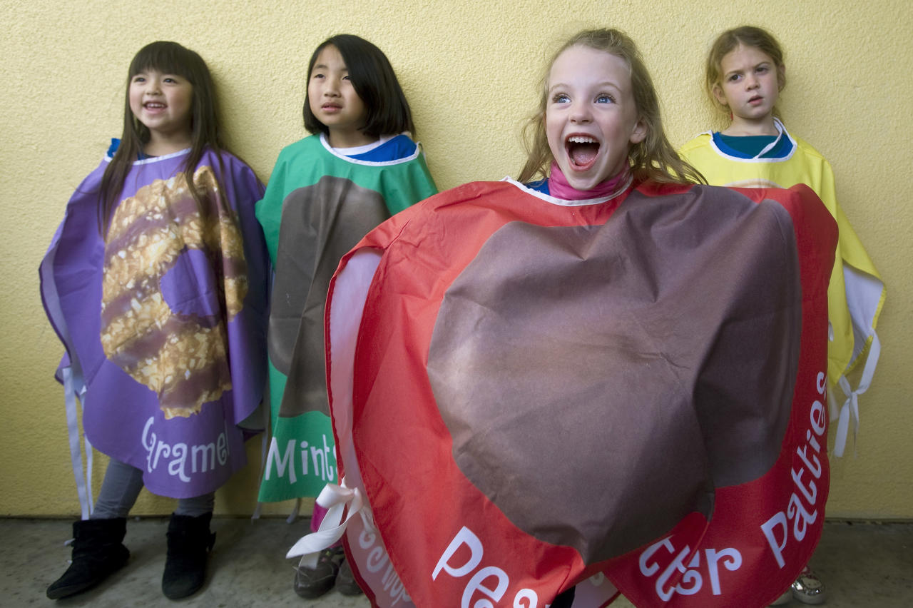 Emily Burch, 7, center, bursts out of a cookie lineup during the 2012 Girl Scouts Cookie Rally in Irvine, Calif. Sunday, Jan. 22, 2012. The event kicks off a year-long celebration of the organization's 100th anniversary. Burch was with other costumed cookies from her Los Alamitos Daisy Troop 2382, from left, Kate Shimabukuro, 7, Alicia Tam, 6, and Lottie Morrison, 6. (AP Photo/Orange County Register, Mindy Schauer)   MAGS OUT; LOS ANGELES TIMES OUT