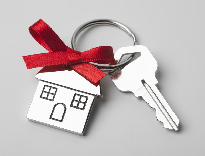 House keys with house shaped keychain with red ribbon on light grey background