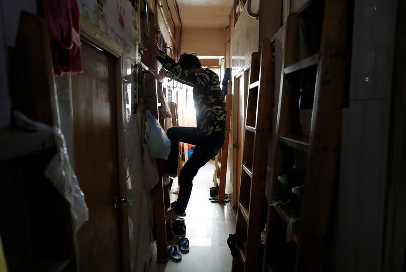 "Simon Wong, 64, climbs out of his 2 square metre subdivided residential unit, known as a ""coffin home"", following the outbreak of the new coronavirus, in Hong Kong"