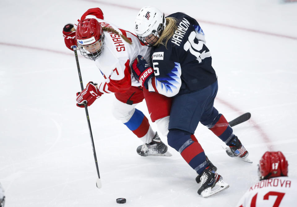 Russia's Kristi Shashkina, left, passes the puck as she is is checked by Savannah Harmon, of the United States, during second period IIHF Women's World Championship hockey action in Calgary, Alberta, Tuesday, Aug. 24, 2021. (Jeff McIntosh/The Canadian Press via AP)