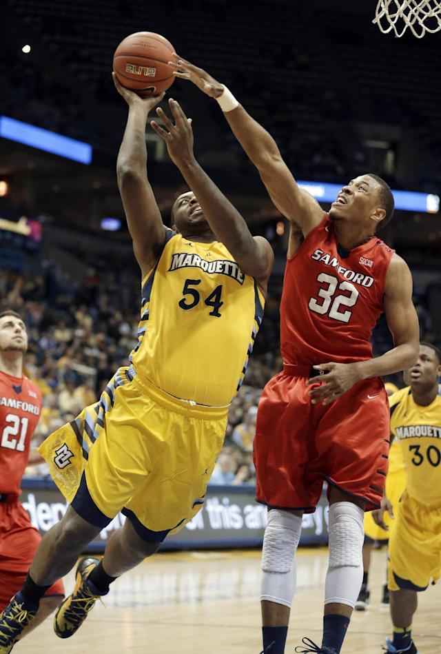 Marquette's Davante Gardner, left, shoots against Samford's Tim Williams (32) during the first half of an NCAA college basketball game Saturday, Dec. 28, 2013, in Milwaukee. (AP Photo/Morry Gash)