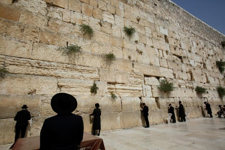 Ultra-Orthodox Jewish worshippers pray in front of the Western Wall in Jerusalem on May 21, 2021