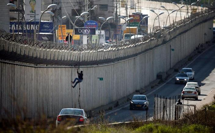 A Palestinian man uses a rope to climb over a section of Israel's controversial separation barrier as many do in search for work (AFP Photo/Thomas Coex)