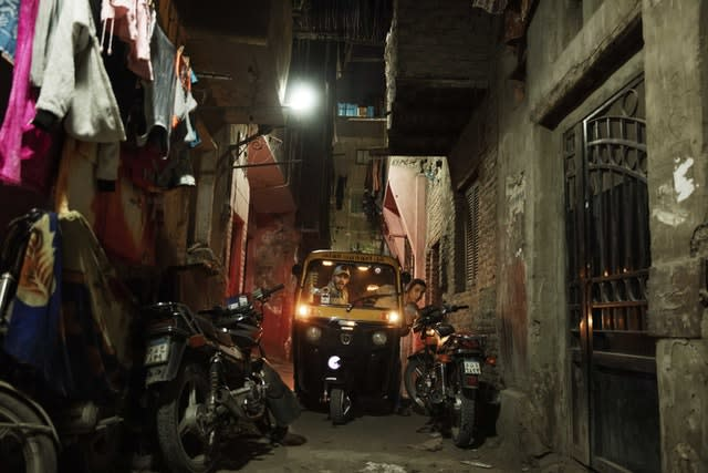 A driver tries to manoeuvre his tuk-tuk in a narrow alleyway of a slum in Cairo, Egypt