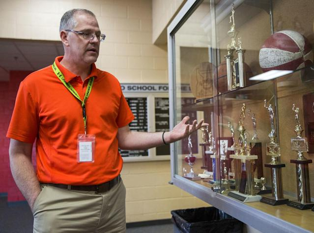 """In this Feb. 7, 2018, photo, administrator Brian Darcy shows off the trophy case at the Idaho School for the Deaf and the Blind in Gooding, Idaho. """"(When) budgets cut, in every school, athletics is the first thing to go,"""" said Brian Darcy, the IESDB administrator. """"It was for us, too."""" Through enthusiastic messaging and government backing, ISDB avoided closure. (Pat Sutphin/The Times-News via AP)"""