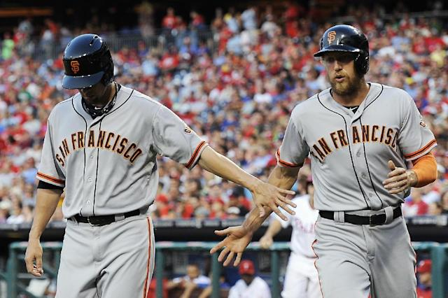 San Francisco Giants' Ryan Vogelsong, left, celebrates Hunter Pence after they scored on a Buster Posey single in the third inning of a baseball game on Monday, July 21, 2014, in Philadelphia. (AP Photo/Michael Perez)