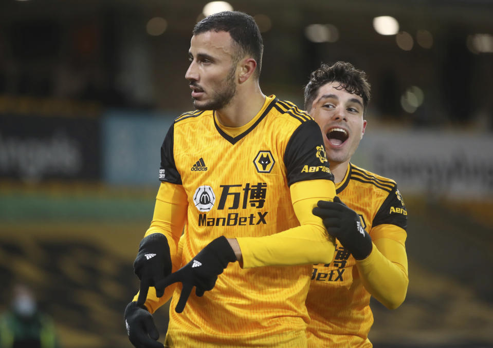 Wolverhampton Wanderers' Romain Saiss, left, celebrates with a teammate after scoring his sides 1st goal of the game during the English Premier League soccer match between Wolverhampton Wanderers and Tottenham Hotspur at Molineux Stadium, in Woverhampton, England, Sunday, Dec. 27, 2020. (Carl Recine/ Pool via AP)
