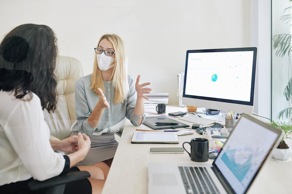 Young businesswoman in glasses and medical mask actively gesturing when explaining idea to collesgue