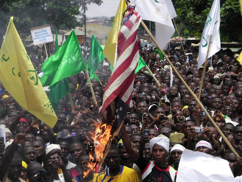 "Muslims burn an American  flag following a protest in Kaduna, Nigeria, Monday, Sept. 24, 2012.  Hundreds of Muslims march peacefully through the streets of a northern Nigerian city to protest an anti-Islam film that denigrates the Prophet Muhammad. The march took place Monday in the city of Kaduna, where hundreds were killed in religious violence following Nigeria's 2011 presidential election. Those protesting left behind graffiti on walls reading: ""Death to the Americans, Death to the Israelites."" (AP Photo/Godwin Attah)"