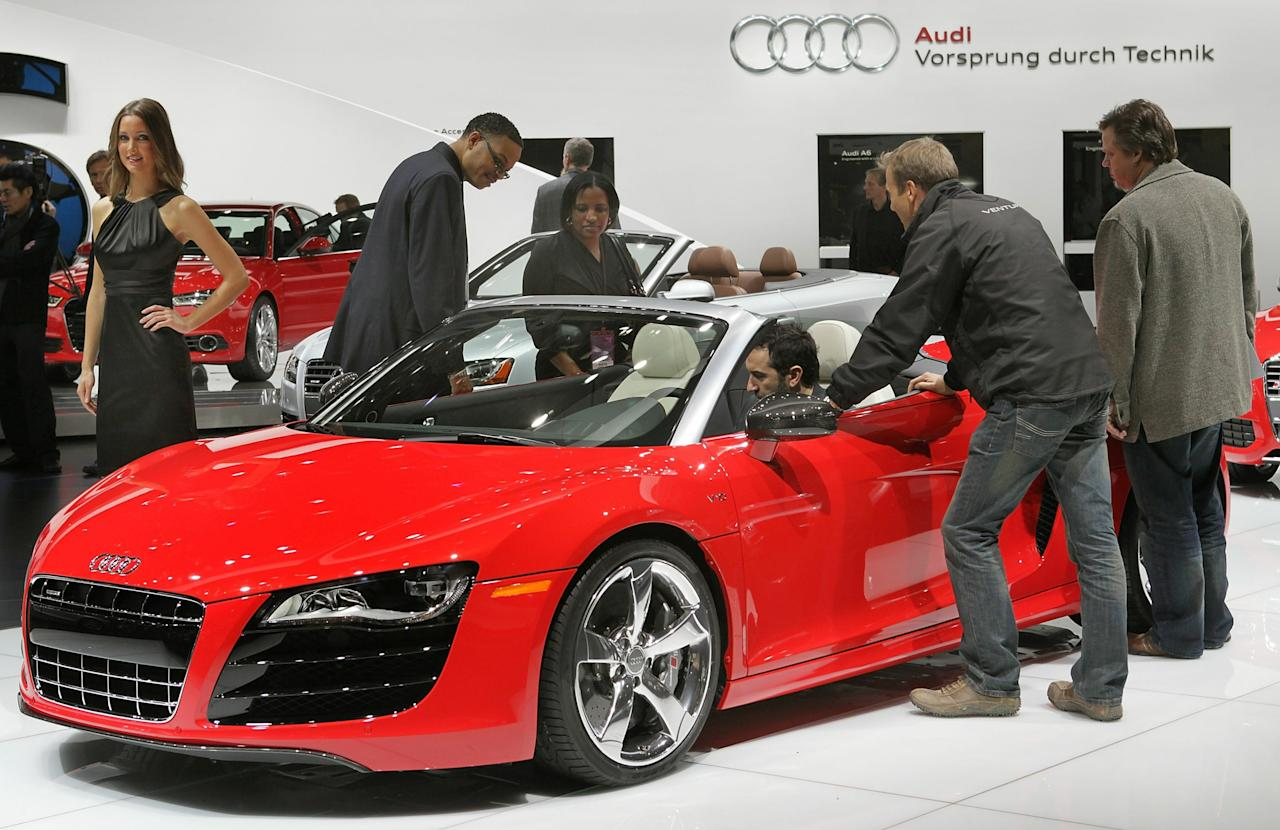 DETROIT, MI - JANUARY 11:  Journalists look over an Audi R8 during the press preview of the North American International Auto Show at the Cobo Center on January 11, 2011 in Detroit, Michigan. The show is currently opened only for media previews and opens to the general public January 15-23.  (Photo by Scott Olson/Getty Images)