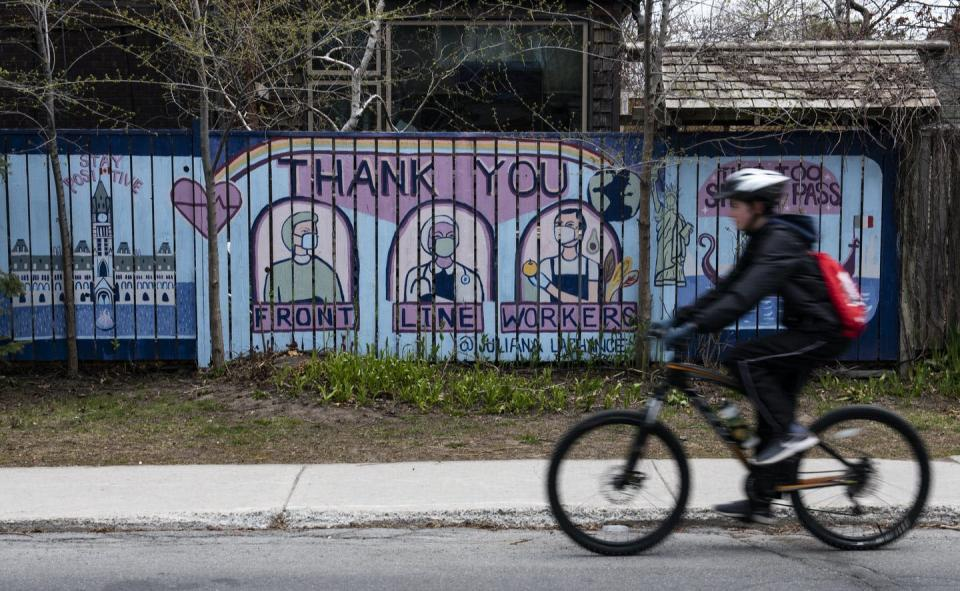 A cyclist passes a mural thanking front-line workers for their efforts during the COVID-19 pandemic