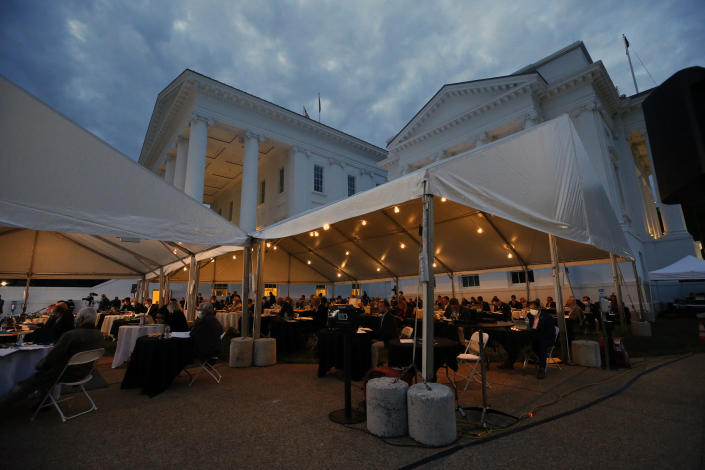 House of Delegates members meet into the evening as they neared the end of the veto session at the Virginia State Capitol in Richmond, Va., Wednesday, April 22, 2020. The House members were meeting outside under a tent instead of the House Chamber in order to practice social distancing due to the COVID-19 outbreak. (Bob Brown/Richmond Times-Dispatch via AP)