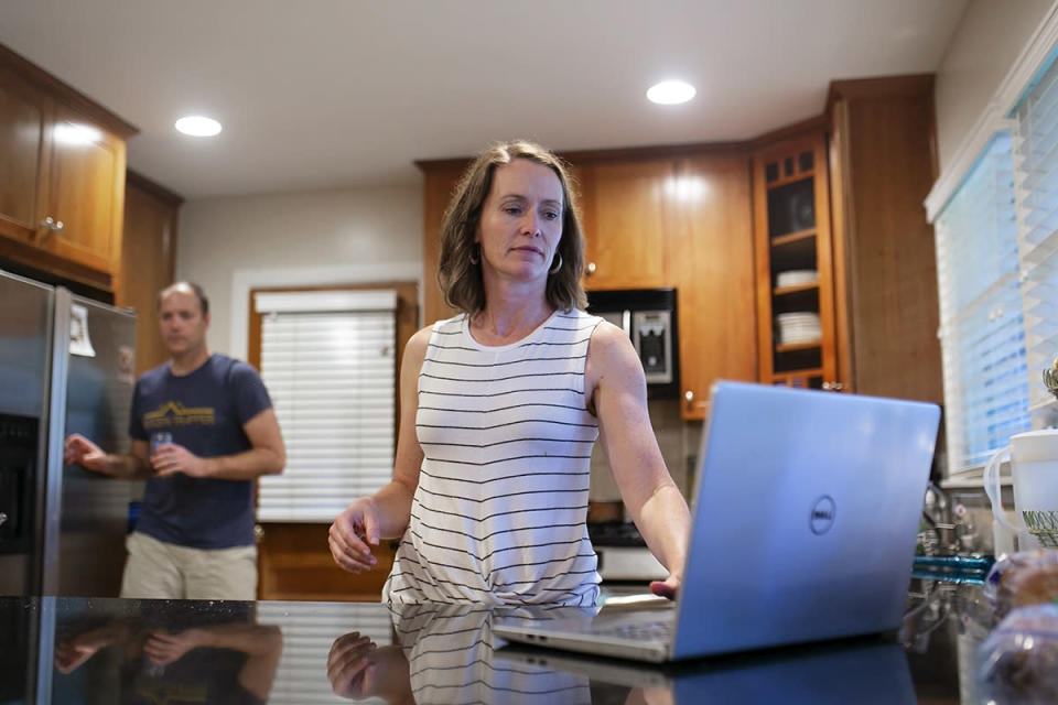 a woman uses a laptop in her kitchen