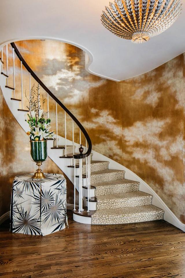 "The entry was ""inspired by the glint of water that can almost be touched,"" explains Malone. A gilded paper with an amazing cloud effect by de Gournay almost needs no help from the HEWN + Fuse Lighting chandelier to illuminate the spiral staircase."