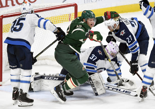 Minnesota Wild's Eric Staal (12) celebrates a goal as Winnipeg Jets' Mathieu Perreault (85), goaltender Connor Hellebuyck (37) and Ehlers (27), of Denmark, watch during the third period of an NHL hockey game Friday, Nov. 23, 2018, in St. Paul, Minn. The Wild won 4-2. (AP Photo/Hannah Foslien)