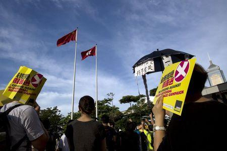 Pro-democracy protesters hold signs during a march to demand lawmakers reject a Beijing-vetted electoral reform package for the city's first direct chief executive election, under Hong Kong flags outside the Legislative Council building in Hong Kong, China June 14, 2015. REUTERS/Tyrone Siu