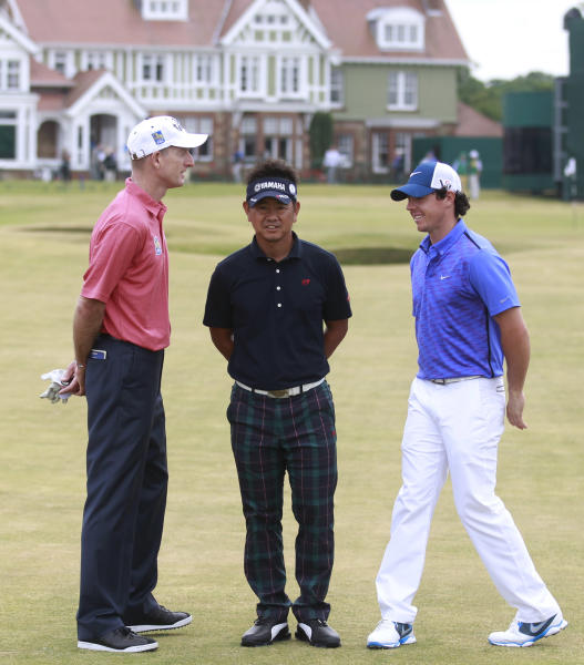 Jim Furyk of the United States, left, Hiroyuki Fujita of Japan, center, and Rory McIlroy of Northern Ireland pose for a photo in front of the club house after a practice round ahead of the British Open Golf Championship at Muirfield, Scotland, Wednesday July 17, 2013. (AP Photo/Peter Morrison)