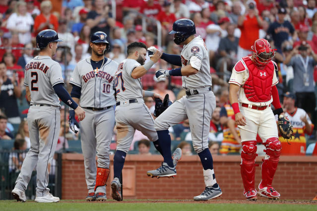 Houston Astros' Carlos Correa is congratulated by teammates Alex Bregman (2), Yuli Gurriel (10) and Jose Altuve (27) after hitting a grand slam as St. Louis Cardinals catcher Andrew Knizner, right, stands by during the third inning of a baseball game Saturday, July 27, 2019, in St. Louis. (AP Photo/Jeff Roberson)
