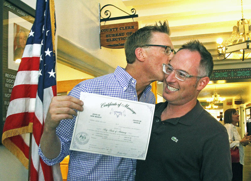 Yon Hudson gives his partner, Alex Hanna, a kiss after they received their marriage license from the Santa Fe County Clerks office on Friday, Aug. 23, 2013. First in line were Santa Fe County Commissioner Liz Stefanics and LInda Siegle. (AP Photo/The New Mexican, Jane Phillips)