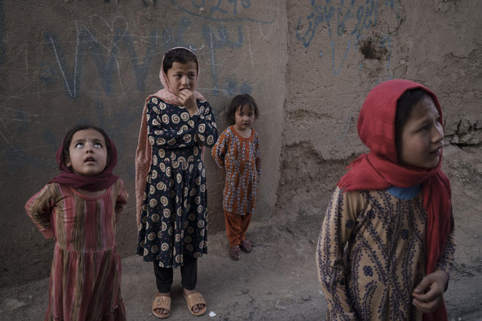Afghan girls look up and listen as a neighbour describes when two men fell from a U.S. Air Force C-17 taking off from Kabul's International Airport on Aug. 16 and landed on the rooftop of his house in Kabul, Afghanistan, Friday, Sept. 17, 2021. (AP Photo/Felipe Dana)