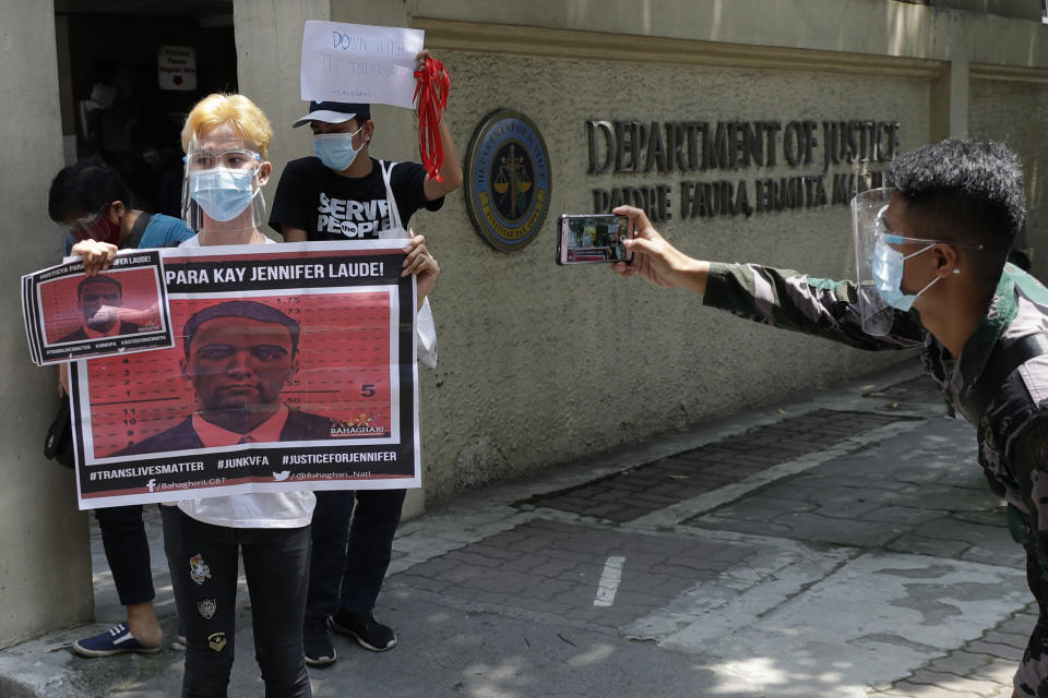 A protester holds a picture of U.S. Marine Lance Cpl. Joseph Scott Pemberton as they hold a rally outside the Department of Justice in Manila, Philippines on Thursday, Sept. 3, 2020. A Philippine court has ordered the early release for good conduct of Pemberton convicted in the 2014 killing of a transgender Filipino which sparked anger in the former American colony. (AP Photo/Aaron Favila)