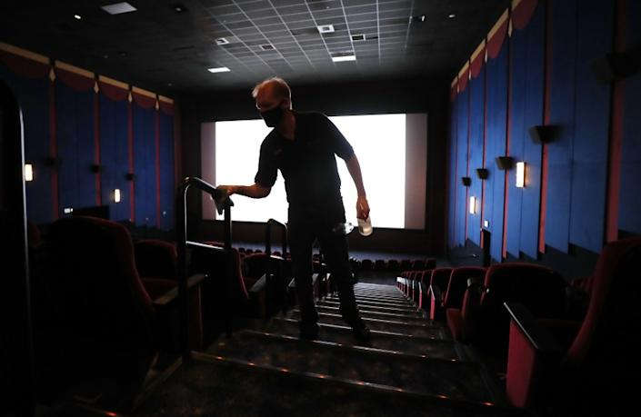 LA MESA, CA - SEPTEMBER 3: Wayne Price cleans handrails in a movie theater on the first day of being open since the closing due to the coronavirus pandemic at Reading Cinemas Grossmont on Thursday, Sept. 3, 2020 in La Mesa, CA. (K.C. Alfred / The San Diego Union-Tribune)