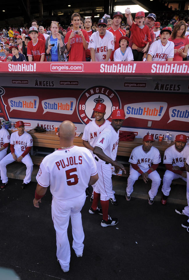 Los Angeles Angels first baseman Albert Pujols (5) is greeted by teammates as he walks into the dugout prior to a baseball game against the Kansas City Royals, Friday, April 6, 2012, in Anaheim, Calif. (AP Photo/Mark J. Terrill)