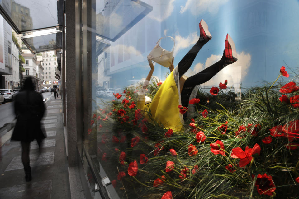 A man walks past the Gucci store window at the Via Montenapoleone fashion district, during the Milan's fashion week in Milan, Italy, Friday, Sept. 25, 2020. (AP Photo/Luca Bruno)