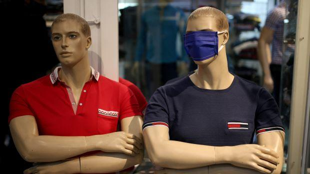 Two mannequins in a store, one wearing a cloth mask over its eyes.
