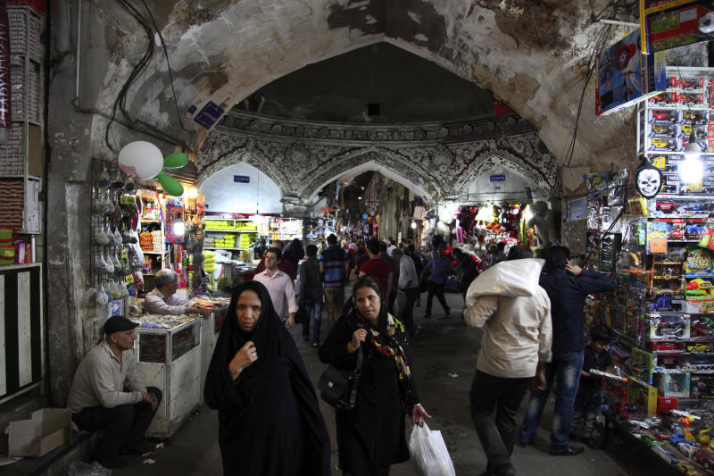 Iranians walk in the old bazaar, in Tehran, Iran, on Sunday, May 12, 2013. On Saturday former President Akbar Hashemi Rafsanjani's made a last minute surprise decision to enter Iran's presidential election process, which now includes more than 680 hopefuls and will culminate June 14 with just a handful of names on the ballot to succeed Mahmoud Ahmadinejad. In one of his first statements since joining the race, Rafsanjani spoke in general terms Sunday of seeking a new ``economic and political'' rebirth in a time of ``foreign threats and sanctions.'' (AP Photo/Vahid Salemi)