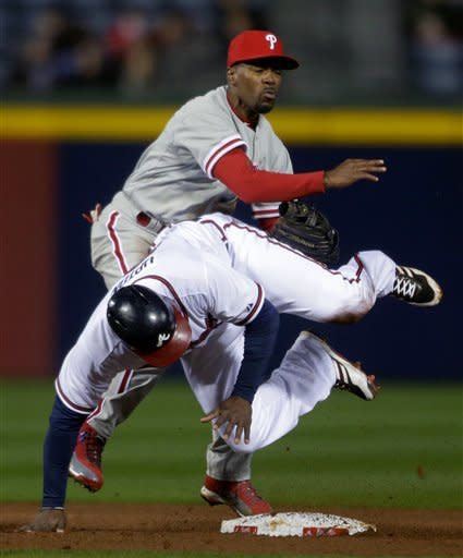 Atlanta Braves' Justin Upton, right, rolls into Philadelphia Phillies' Jimmy Rollins after sliding into second base on a double play in the fourth inning of a baseball game, Thursday, April 4, 2013, in Atlanta. (AP Photo/David Goldman)