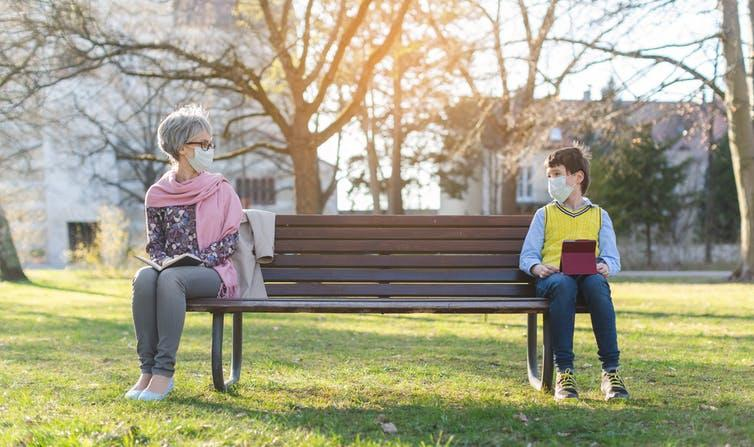 Grandmother and grandson sitting at opposite ends of a park bench.