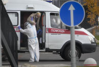 A medical worker helps a patient suspected of having coronavirus to leave an ambulance at a hospital in Kommunarka, outside Moscow, Russia, Tuesday, Oct. 12, 2021. Russia hit another record of daily coronavirus deaths Tuesday as the country struggled with a rapid surge of infections and lagging vaccination rates, but authorities have been adamant that there would be no new national lockdown. (AP Photo/Alexander Zemlianichenko)