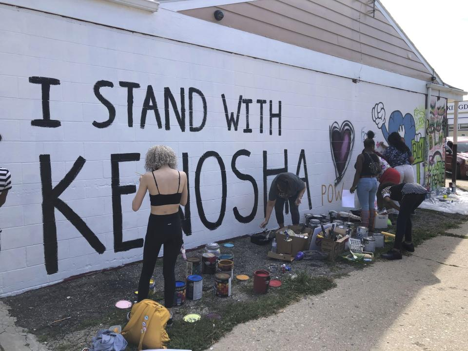 """Volunteers paint murals on boarded-up businesses in Kenosha, Wis., on Sunday, Aug. 30, 2020, at an """"Uptown Revival."""" The event was meant to gather donations for Kenosha residents and help businesses hurt by violent protests that sparked fires across the city following the police shooting of Jacob Blake. (AP Photo/ Russell Contreras)"""