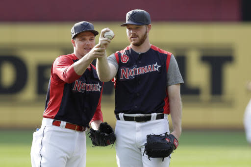 Sonny Gray, left, of the Cincinnati Reds, and Brandon Woodruff, of the Milwaukee Brewers, compare their baseball holds during batting practice for the MLB All-Star baseball game, Monday, July 8, 2019, in Cleveland. The game will be played Tuesday. (AP Photo/Tony Dejak)
