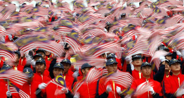 Malaysian students wave national flags during a rehearsal for Malaysia Day celebrations at Independence Square in Kuala Lumpur, Malaysia, Wednesday, Sept. 14, 2011. The country celebrates the holiday on Sept. 16, to commemorate the formation of the Malaysia federation which was announced on the same date in 1963. (AP Photo/Lai Seng Sin)