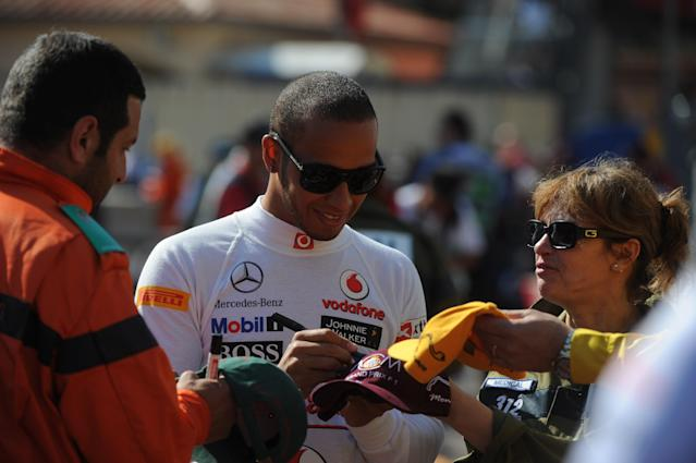 McLaren Mercedes' British driver Lewis Hamilton signs autographs in the pits during first practice session at the Circuit de Monaco on May 24, 2012 in Monte Carlo ahead of the Monaco Formula One Grand Prix. AFP PHOTO / DIMITAR DILKOFFDIMITAR DILKOFF/AFP/GettyImages