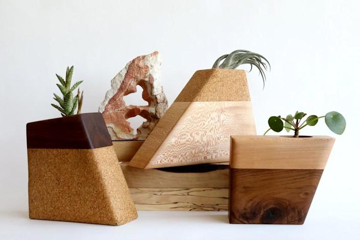 """LOS ANGELES, CA - JULY 09: C.C. Boyce, 47, creates """"Planturns"""" - custom-made wood urns for cremation remains, in her studio in the garment district, on Friday, July 9, 2021 in Los Angeles, CA. Left: Walnut top and cork bottom. Center: Cork top and sycamore bottom. Right: Sycamore top and walnut bottom. Boyce's urns, which can be used for both pets and people, are unique in that they can be used as planters. C.C. is founder of Boyce Studio in the garment district downtown. (Gary Coronado / Los Angeles Times)"""