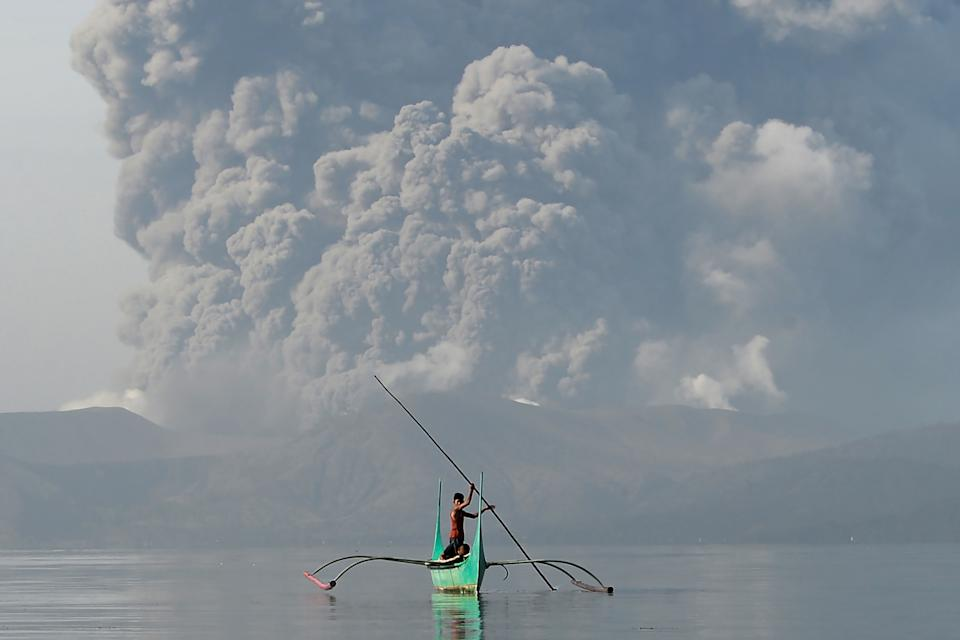 """TOPSHOT - A youth living at the foot of Taal volcano rides an outrigger canoe while the volcano spews ash as seen from Tanauan town in Batangas province, south of Manila, on January 13, 2020. - The Philippines was on alert January 13 for the """"explosive eruption"""" of a volcano south of Manila, which officials said could be imminent after a massive column of ash forced a halt to flights at the capital's main airport. (Photo by Ted ALJIBE / AFP) (Photo by TED ALJIBE/AFP via Getty Images)"""