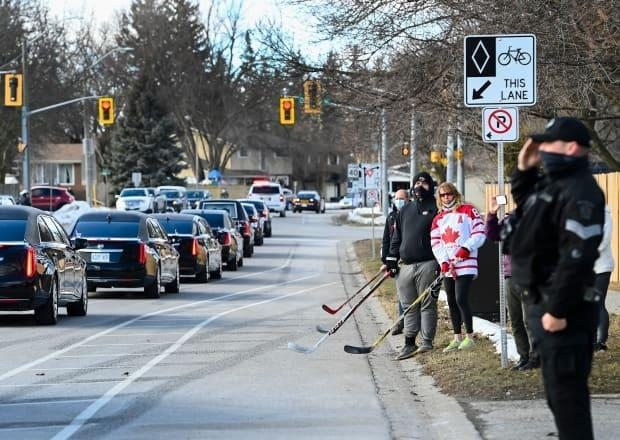 People gathered along the sidewalk to pay their respects as the funeral procession for Walter Gretzky passed by in Brantford, Ont., on Saturday afternoon.