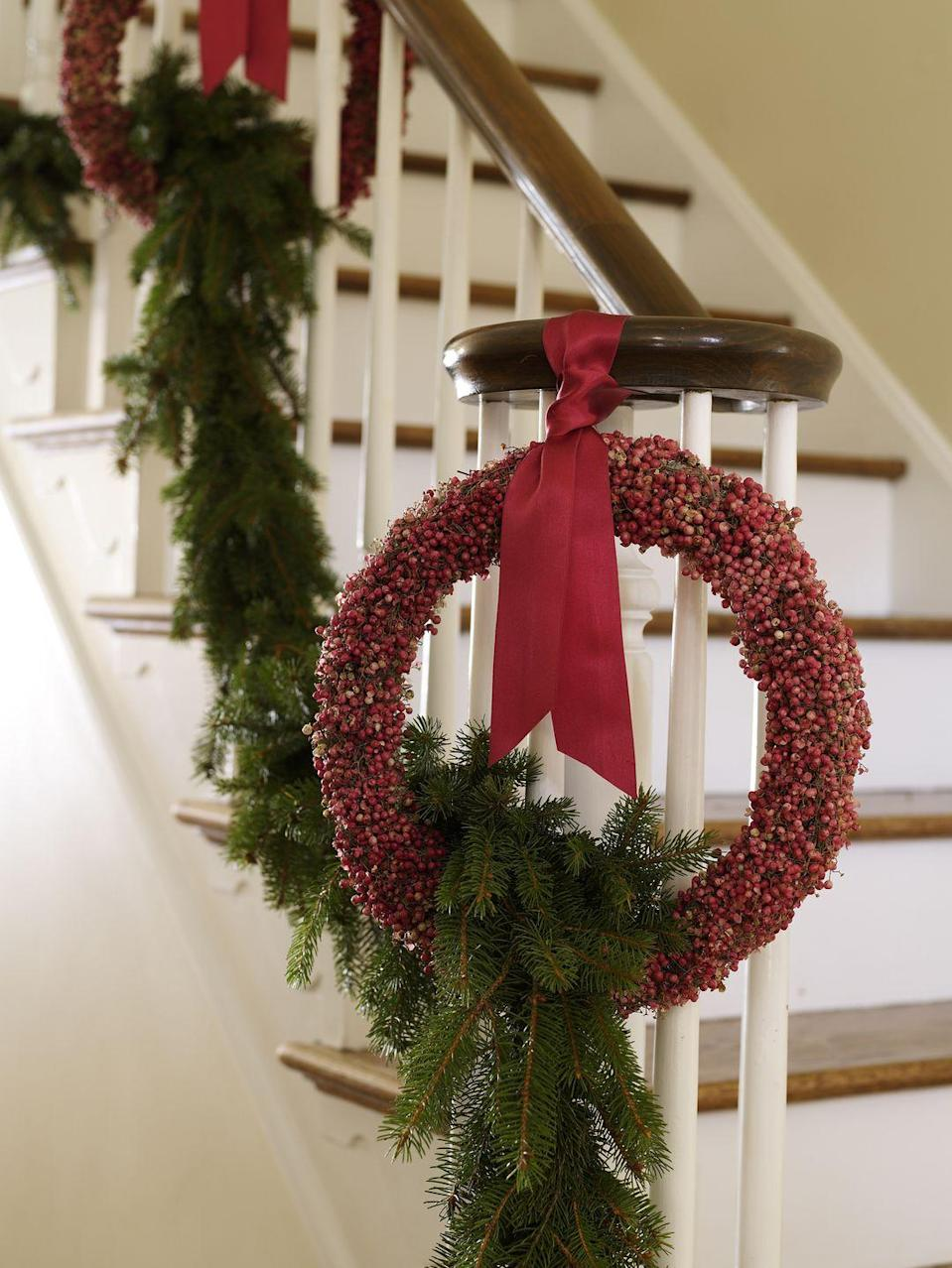 """<p>For a classic look that works from Thanksgiving through Christmas, combine cranberry-studded wreaths with a simple pine garland. </p><p><a class=""""link rapid-noclick-resp"""" href=""""https://www.amazon.com/Afloral-Natural-Norfolk-Christmas-Garland/dp/B07H9GL1CV?tag=syn-yahoo-20&ascsubtag=%5Bartid%7C10072.g.34479907%5Bsrc%7Cyahoo-us"""" rel=""""nofollow noopener"""" target=""""_blank"""" data-ylk=""""slk:SHOP PINE GARLAND"""">SHOP PINE GARLAND</a></p>"""