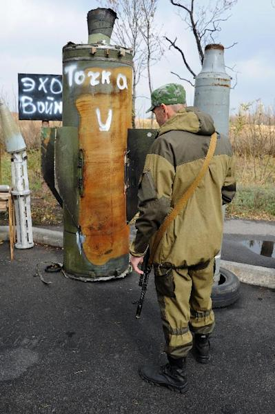 A pro-Russian separatist fighter stands in front of part of a ballistic missile on October 21, 2014, in Donetsk, Ukraine (AFP Photo/Dominique Faget)