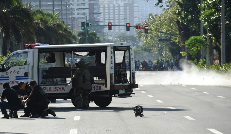 Members of police bomb disposal unit detonate a suspicious package along Roxas Boulevard near the US embassy in Manila on November 28, 2016