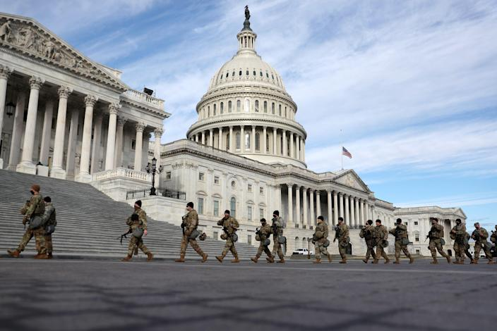 Members of Virginia National Guard walk by the U.S. Capitol on Jan 17, 2021 in Washington, DC. After last week's riots at the U.S. Capitol Building, the FBI has warned of additional threats in the nation's capital and in all 50 states. According to reports, as many as 25,000 National Guard soldiers will be guarding the city as preparations are made for the inauguration of Joe Biden as the 46th U.S. President.
