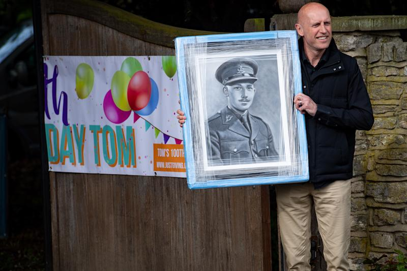 A man delivers a gift to the home of Captain Tom Moore in Bedford as he celebrates his 100th birthday.