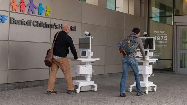 PHOTO: Two staff members wheel Amwell telemedicine carts into the entrance of the University of California San Francisco Benioff Children's Hospital during an outbreak of the COVID-19 coronavirus, March 16, 2020. (Smith Collection/Gado/Getty Images)